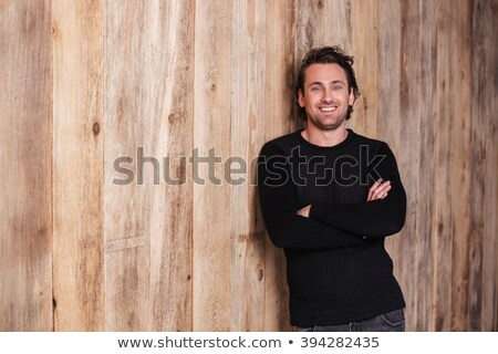 Smiling attractive man in black jumper standing with hands folded  Stock photo © deandrobot