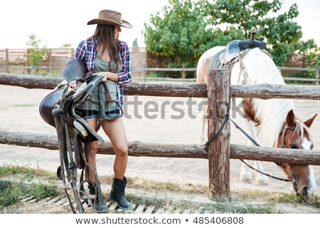 Happy woman cowgirl standing and holding saddle for riding horse Stock photo © deandrobot