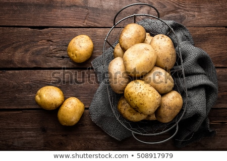 Raw potato in basket on wooden table, top view Stock photo © yelenayemchuk