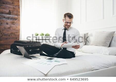 бизнесмен кровать рабочих таблетка ноутбука номер в отеле Сток-фото © tommyandone