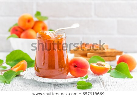 apricot jam and fresh fruits with leaves on white wooden table stock photo © yelenayemchuk
