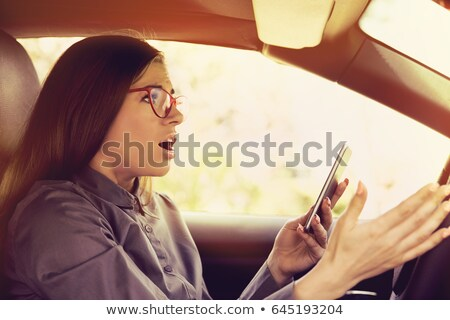Woman driving and texting on mobile smartphone Stock photo © stevanovicigor