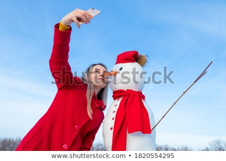 woman taking photo of snowman Stock photo © IS2