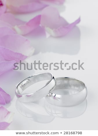 silver wedding rings resting next to flower petals stock photo © monkey_business