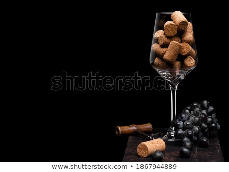 wine glass with corks inside with vintage corkscrew opener and dark grapes on wooden board on black stock photo © denismart