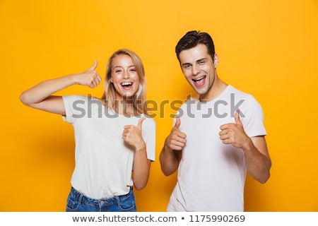 Happy young couple standing isolated over yellow Stock photo © deandrobot
