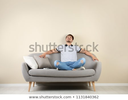 Man Relaxing On Sofa Operating Air Conditioner Stock photo © AndreyPopov