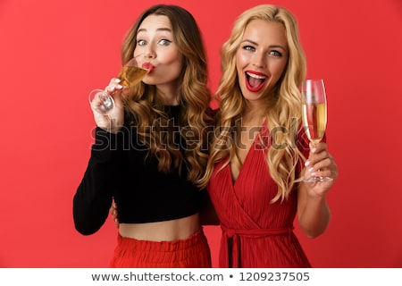 happy young friends women standing isolated over red background drinking champagne stock photo © deandrobot