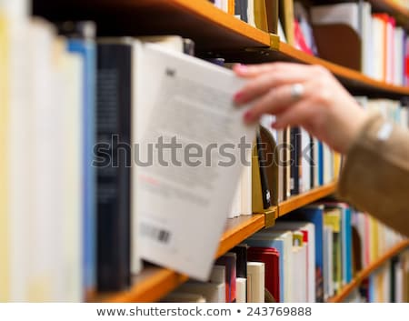 Woman choosing books from shelf in library Stock photo © Kzenon