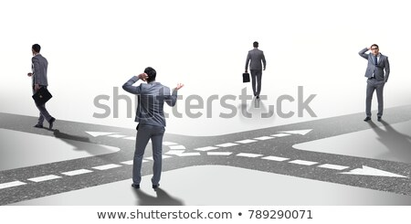 Young businessman at crossroads in uncertainty concept Stock photo © Elnur