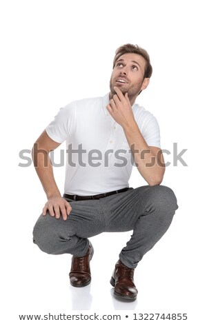 smiling crouched casual man looks up and thinks Stock photo © feedough