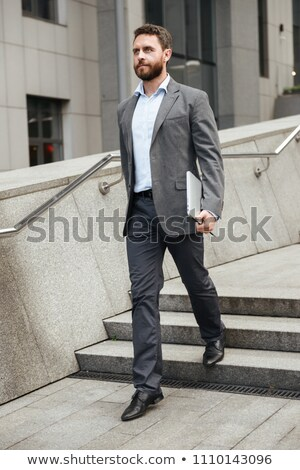 Full length photo of business man in formal wear holding silver  Stock photo © deandrobot