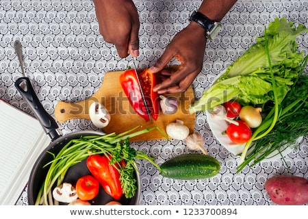 young man chopping vegetables in the kitchen and preparing healt stock photo © boggy