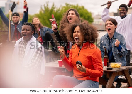 Young ecstatic hockey fans watching broadcast of world championship outdoors Stock photo © pressmaster