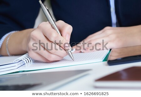 Hand of young businesswoman with pen making notes on page of notebook Stock photo © pressmaster