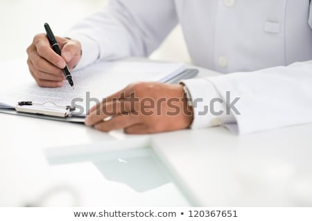 Сток-фото: Hand Of Professional Clinician With Pen Over Clipboard With Medical Document