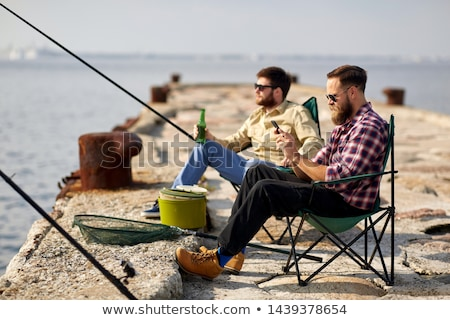friends with smartphone and beer fishing on pier Stock photo © dolgachov