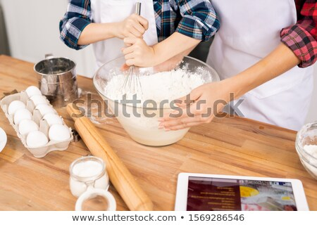 Hands of young woman holding bowl while her little son whisking eggs with flour Stock photo © pressmaster