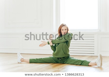 Horizontal shot of flexible young sporty woman stretches hands and legs after cardio workout, warms  Stock photo © vkstudio