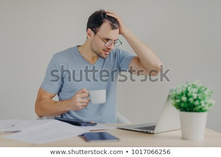 Desperate young male has financial crisis, scratches head in tension, tries to find solution, search Stock photo © vkstudio