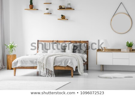 Comfortable, big, wooden bed with linen, pillows and blanket, nightstand beside and round mirror. Stock photo © ruslanshramko
