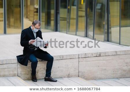 Horizontal outdoor shot of businessman or entrepreneur poses outdoor at street, reads newspaper with Stock photo © vkstudio