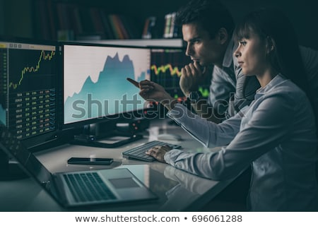 Man and Woman Brokers Analyzing Trades on Chart Stock photo © robuart
