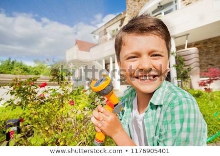 Boy using a garden hose Stock photo © lovleah