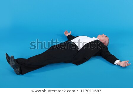mature man in suit lying on his back with arms wide apart against blue background Stock photo © photography33