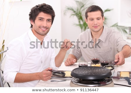 man cooking raclette at the table stock photo © photography33