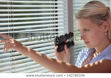 Stock photo: Nosy woman peering through some blinds