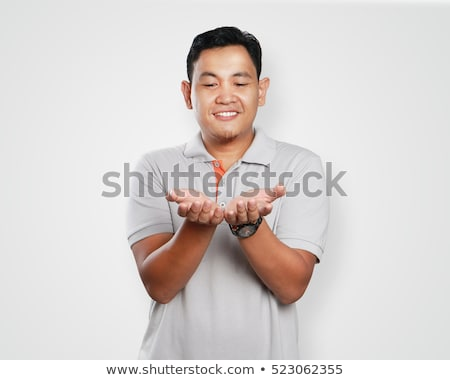 portrait of cute handsome man gesturing with his hands and givin stock photo © meinzahn