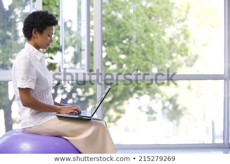 Fit young woman concentrating on balance using exercise ball Stock photo © darrinhenry