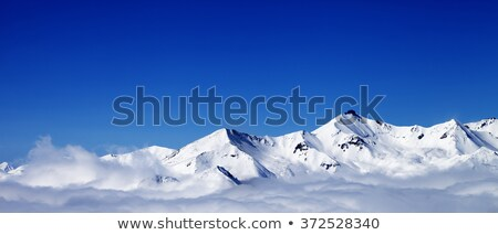 winter snowy mountains in clouds at nice day stock photo © bsani