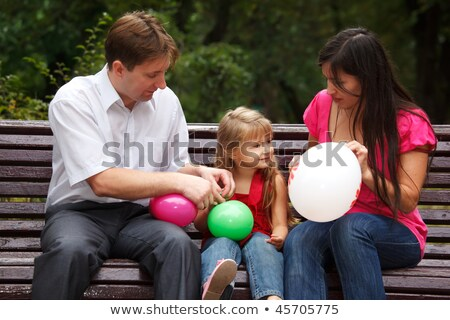 Parents together with daughter on bench in park in afternoon. In hands multi-coloured balloons. Stock photo © Paha_L