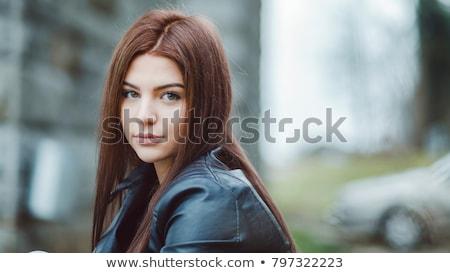 Serene woman with long brown hair stares at camera Stock photo © dash
