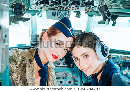 Portrait of young pilot and beautiful stewardess inside airplane cabin Stock photo © deandrobot