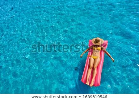 Woman in yellow bikini on floating mat Stock photo © bluering