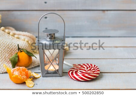 Christmas still life with lantern, plaid, lollipop, tangerine an Stock photo © Yatsenko