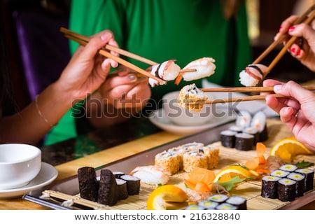 vrouw · eetstokjes · sushi · glimlachend · jonge - stockfoto © fisher