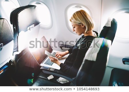 Businesswoman in business class of the aircraft works at a lapto Stock photo © studiostoks