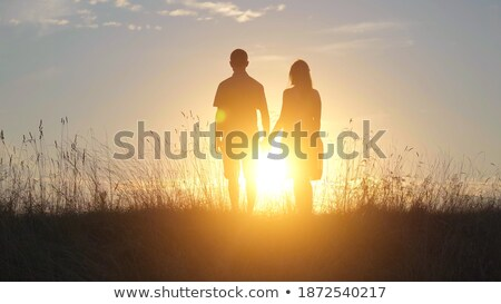 Silhouette of a couple of lovers standing in the sea against sun Stock photo © IMaster
