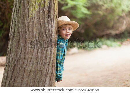 boy wearing cowboy hat behind tree stock photo © is2