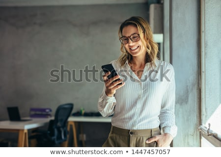 Stock photo: Smiling young woman using mobile phone