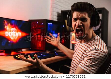 Yandan görünüş öfkeli oynama video oyunları bilgisayar çığlık atan Stok fotoğraf © deandrobot