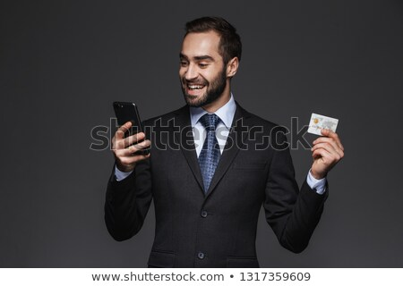 image of confident businessman 30s in suit using credit card and stock photo © deandrobot