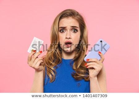 Displeased young woman posing isolated over pink background wall holding money and credit card. Stock photo © deandrobot