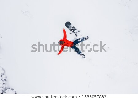 Aerial view of a man lying in the snow next to his snowboard Stock photo © vlad_star