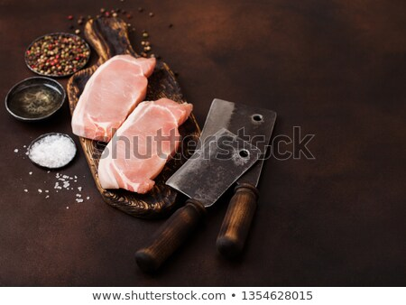 Raw pork loin chops on old vintage chopping board with knife and fork on rusty background. Salt and  Stock photo © DenisMArt