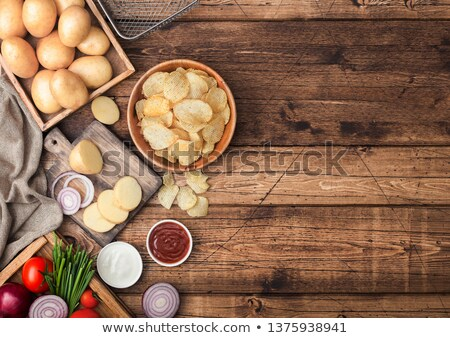 Fresh organic homemade potato crisps chips in wooden bowl with sour cream and red onions and spices  Stock photo © DenisMArt